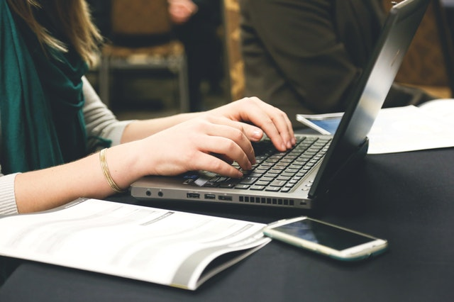 Dievča so zeleným šálom píše na notebooku